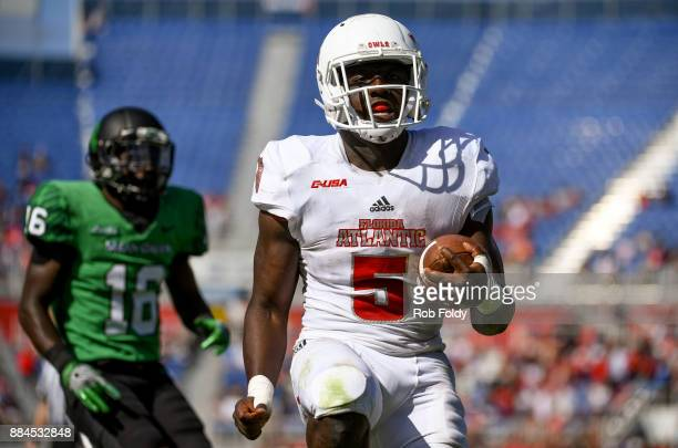 Devin Singletary of the Florida Atlantic Owls rushes for a touchdown past Kemon Hall of the North Texas Mean Green during the Conference USA...