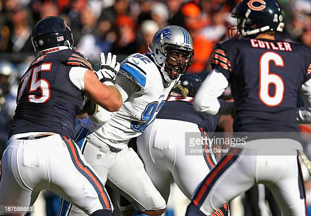 Devin Taylor of the Detroit Lions rushes against Kyle Long of the Chicago Bears as Jay Culter looks to pass at Soldier Field on November 10 2013 in...