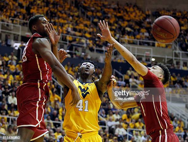 Devin Williams of the West Virginia Mountaineers battles for a rebound against Jamuni McNeace and Dante Buford of the Oklahoma Sooners during the...