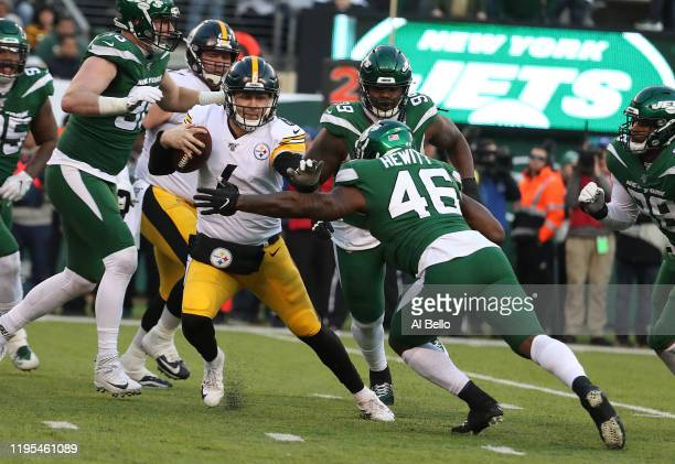 Devlin Hodges of the Pittsburgh Steelers eludes Neville Hewitt of the New York Jets during their game at MetLife Stadium on December 22, 2019 in East...
