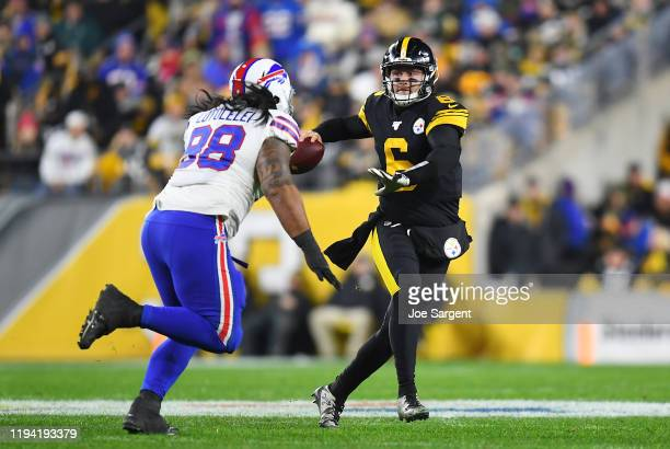 Devlin Hodges of the Pittsburgh Steelers looks to pass as he is pressured by Star Lotulelei of the Buffalo Bills during the first half in the game at...
