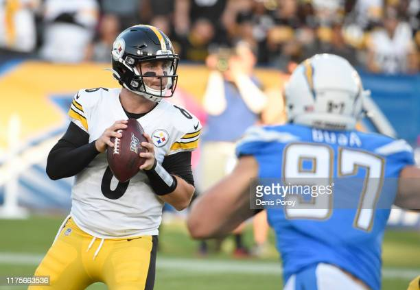 Devlin Hodges of the Pittsburgh Steelers looks to pass under pressure from Joey Bosa of the Los Angeles Chargers in the first quarter at Dignity...