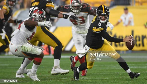 Devlin Hodges of the Pittsburgh Steelers scrambles out of the pocket under pressure from Devante Bond of the Tampa Bay Buccaneers in the second half...