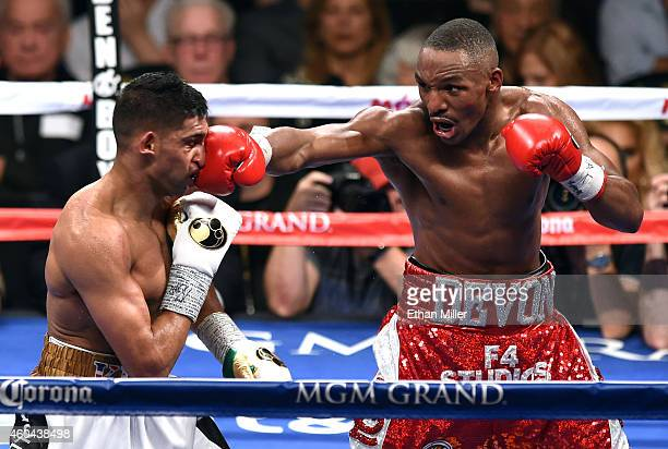 Devon Alexander hits Amir Khan during the 10th round of their welterweight bout at the MGM Grand Garden Arena on December 13 2014 in Las Vegas Nevada...