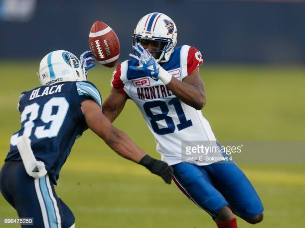 Devon Bailey of the Montreal Alouettes battles Matt Black of the Toronto Argonauts for the ball during a CFL preseason game at BMO field on June 8...