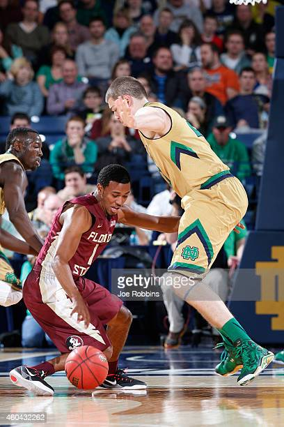 Devon Bookert of the Florida State Seminoles drives to the basket against Martinas Geben of the Notre Dame Fighting Irish during the first half of...