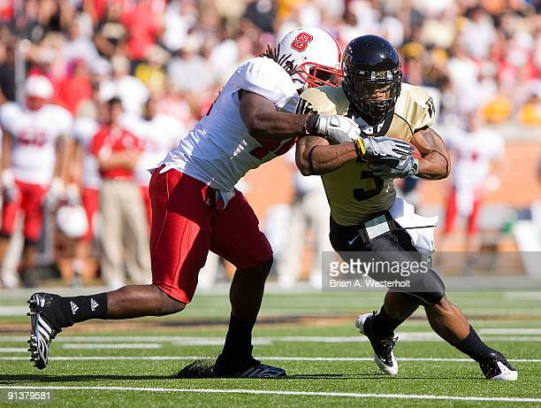 Devon Brown of the Wake Forest Demon Deacons is wrapped up fromk behind by Dwayne Maddox of the North Carolina State Wolfpack at BBT Field on October...