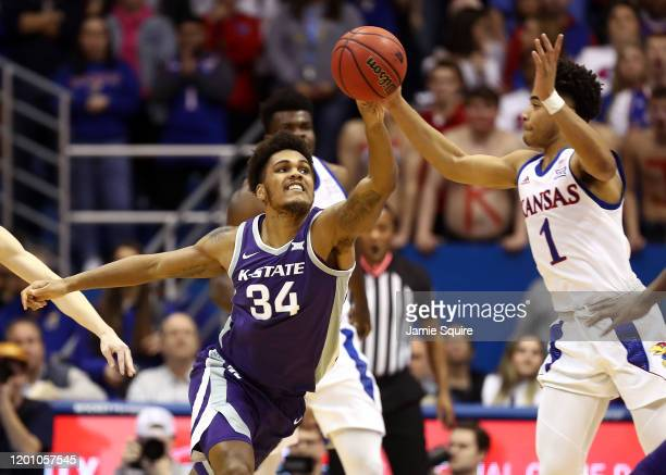 Devon Dotson of the Kansas Jayhawks battles Levi Stockard III of the Kansas State Wildcats for a loose ball during the game at Allen Fieldhouse on...