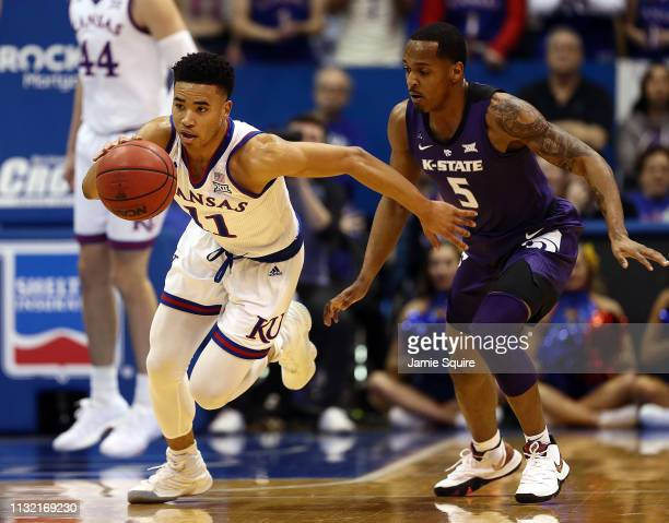 Devon Dotson of the Kansas Jayhawks drives on a fast break as Barry Brown Jr #5 of the Kansas State Wildcats defends during the game at Allen...