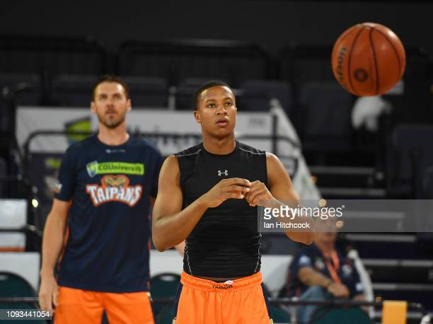 Devon Hall of the Taipans and Alex Loughton of the Taipans warm up before the start of the round 13 NBL match between the Cairns Taipans and...