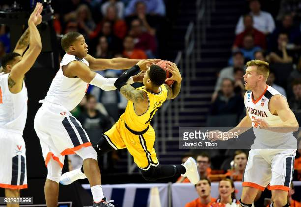 Devon Hall of the Virginia Cavaliers battles for possession with Jairus Lyles of the UMBC Retrievers during the first round of the 2018 NCAA Men's...