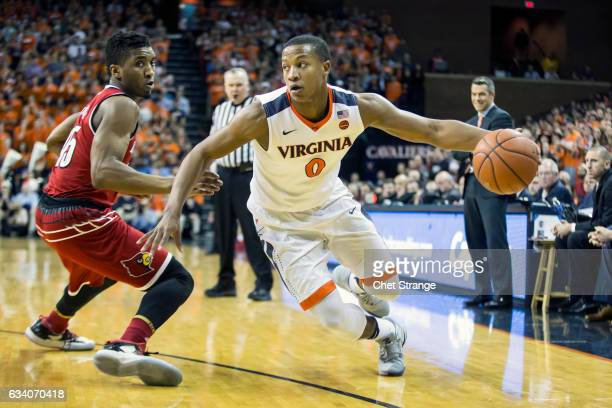 Devon Hall of the Virginia Cavaliers drives the ball past Donovan Mitchell of the Louisville Cardinals during a game at John Paul Jones Arena on...