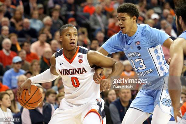 Devon Hall of the Virginia Cavaliers is defended by Cameron Johnson of the North Carolina Tar Heels in the second half during a game at John Paul...