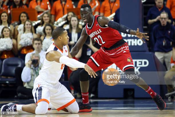 Devon Hall of the Virginia Cavaliers passes around Deng Adel of the Louisville Cardinals in the first half during a game at John Paul Jones Arena on...