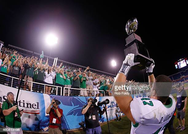Devon Johnson of the Marshall Thundering Herd presents the championship trophy to fans after the game against the Northern Illinois Huskies at FAU...