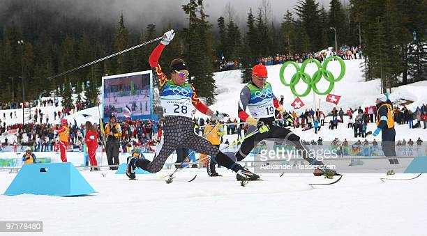 Devon Kershaw of Canada and Tobias Angerer of Germany cross the finish line during the Men's 50 km Mass Start Classic crosscountry skiing on day 17...