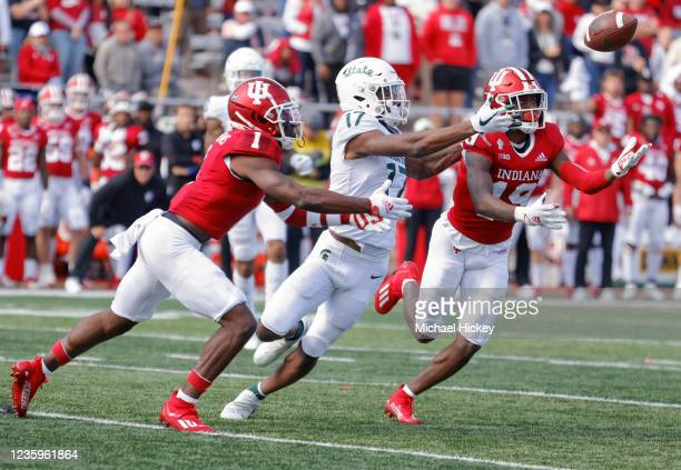 Devon Matthews and Josh Sanguinetti of the Indiana Hoosiers reach for the ball against Tre Mosley of the Michigan State Spartans during the game at...