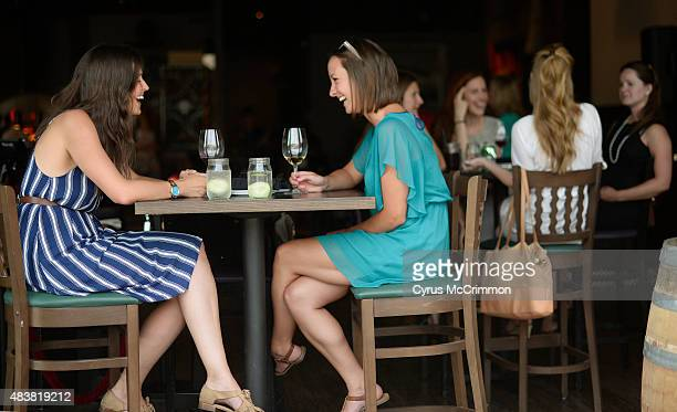 Devon McFadden left and Fiona Spezia enjoy a glass of wine while seated in the open windows at new restaurant Brik on York located at 2223 E Colfax...