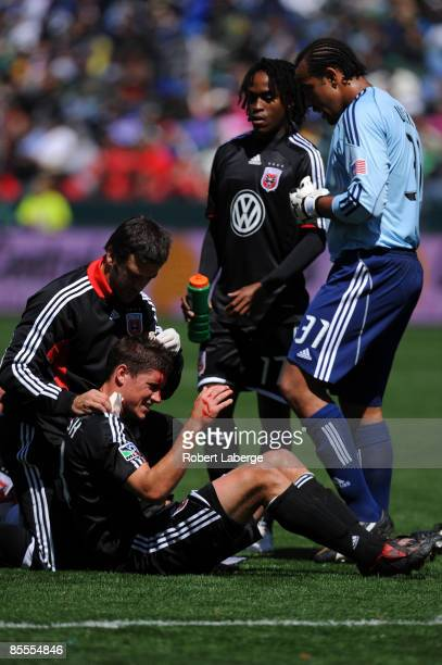 Devon McTavish of DC United gets looked at by a trainer after colliding with his teammate Greg Janicki as Thabiso Khumalo and Josh Wicks look on...