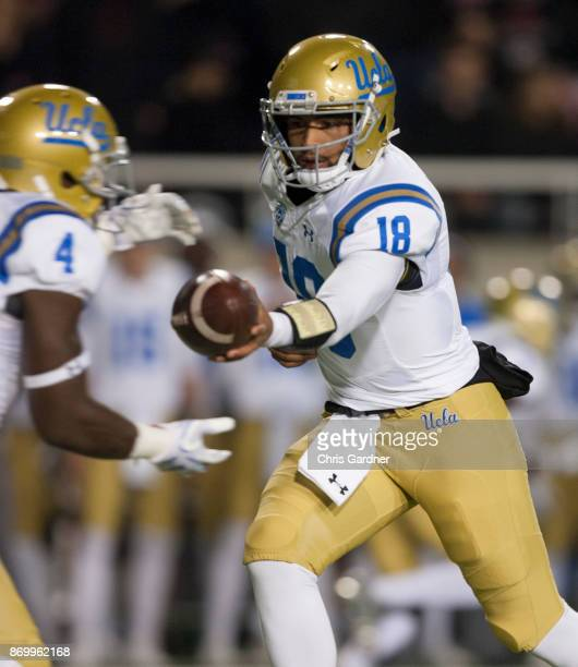 Devon Modster of the UCLA Bruins hands off to Bolu Olrunfunmi against the the Utah Utes at RiceEccles Stadium on November 3 2017 in Salt Lake City...