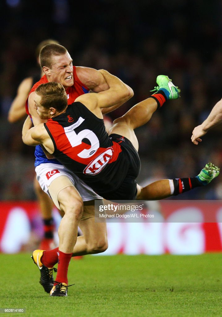 Devon Smith of Essendon tackles Tom McDonald of the Demons during the round 6 AFL match between the Essendon Bombers and Melbourne Demons at Etihad Stadium on April 29, 2018 in Melbourne, Australia.