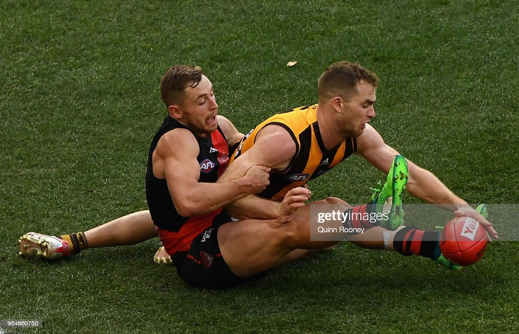 Devon Smith of the Bombers and Tom Mitchell of the Hawks compete for the ball during the round seven AFL match between the Essendon Bombers and the Hawthorn Hawks at Melbourne Cricket Ground on May 5, 2018 in Melbourne, Australia.
