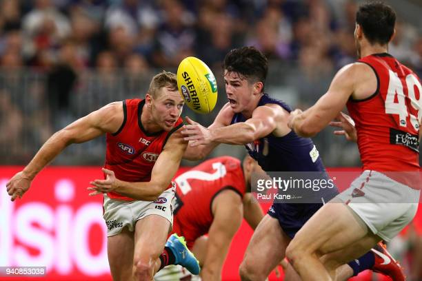 Devon Smith of the Bombers handballs against Andrew Brayshaw of the Dockers during the round two AFL match between the Fremantle Dockers and the...