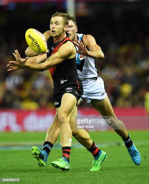 Devon Smith of the Bombers handballs in front of Brad Ebert of Port Adelaide during the round four AFL match between the Essendon Bombers and the...