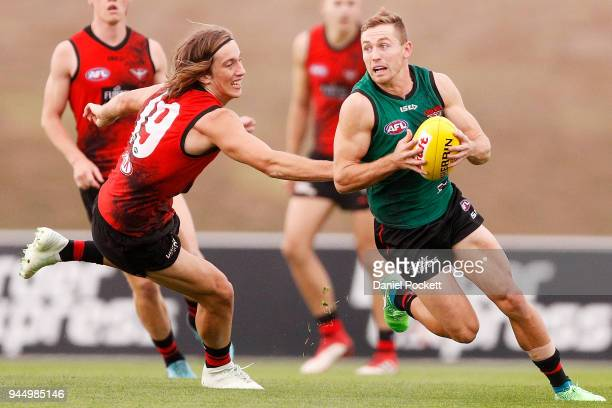 Devon Smith of the Bombers runs with the ball under pressure from Kobe Mutch of the Bombers during an Essendon Bombers AFL training session at the...