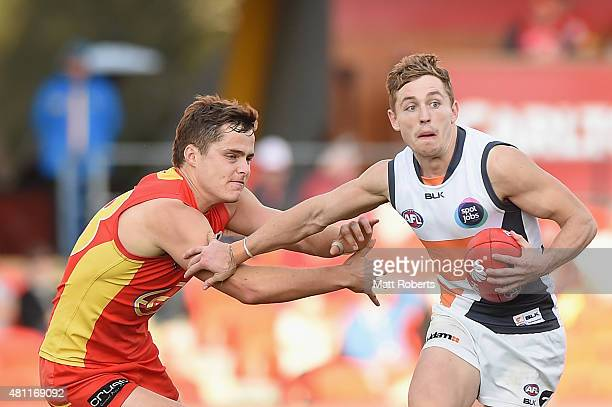 Devon Smith of the Giants takes on the defence during the round 16 AFL match between the Gold Coast Suns and the Greater Western Sydney Giants at...