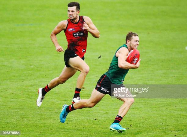 Devon Smith runs with the ball away from Jackson Merrett during the Essendon Bombers AFL IntraClub Match at The Hangar on February 10 2018 in...