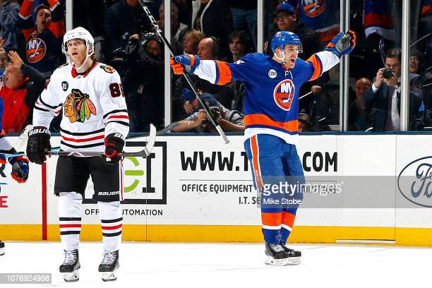 Devon Toews of the New York Islanders celebrates his game winning goal during overtime to give his team a 3-2 win as Patrick Kane of the Chicago...