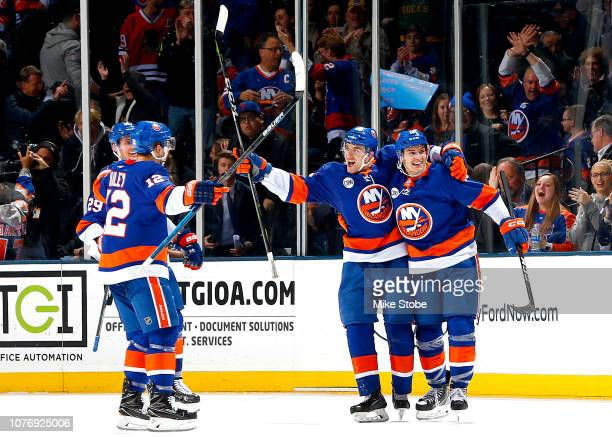 Devon Toews of the New York Islanders is congratulated by his teammates Brock Nelson Josh Bailey and Mathew Barzal after scoring the game winning...