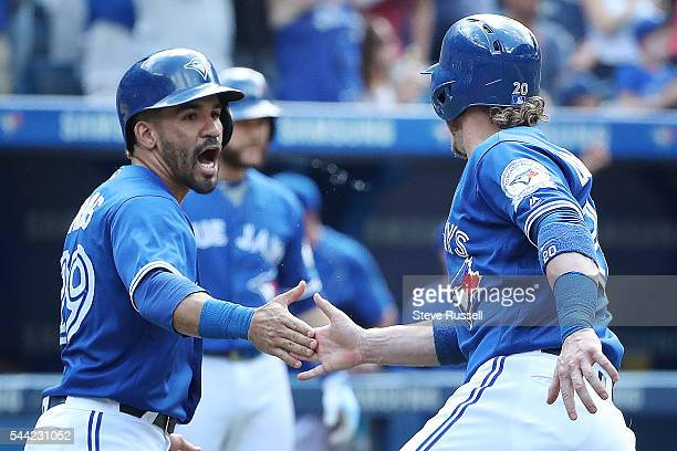 Devon Travis and Josh Donaldson celebrate after being driven home by a Michael Saunders double as the Toronto Blue Jays beat the Cleveland Indians...