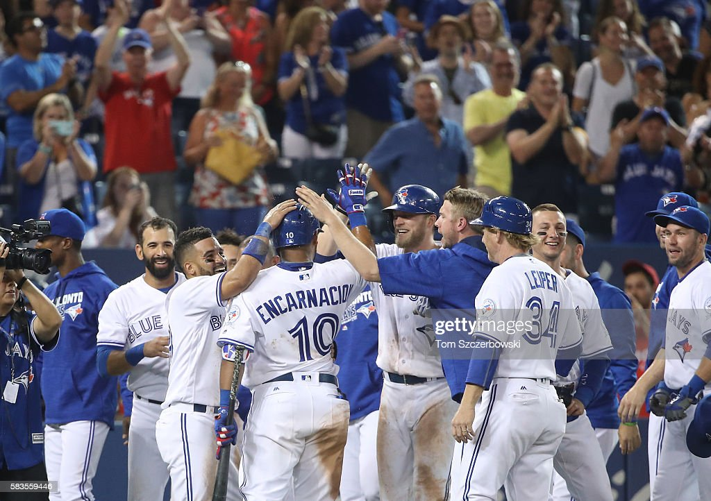Devon Travis #29 of the Toronto Blue Jays and Edwin Encarnacion #10 are congratulated by teammates after scoring the game-winning run on a wild pitch in the twelfth inning during MLB game action against the San Diego Padres on July 26, 2016 at Rogers Centre in Toronto, Ontario, Canada.