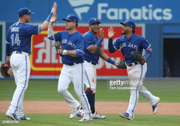 Devon Travis of the Toronto Blue Jays celebrates their victory with teammates during MLB game action against the Washington Nationals at Rogers...