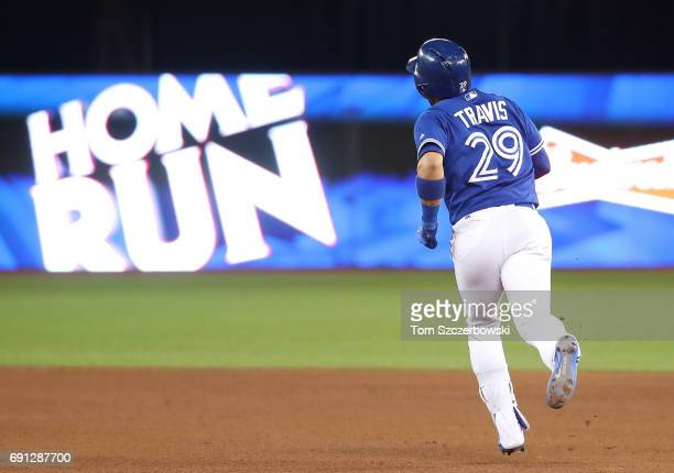 Devon Travis of the Toronto Blue Jays circles the bases after hitting a tworun home run in the seventh inning during MLB game action against the...