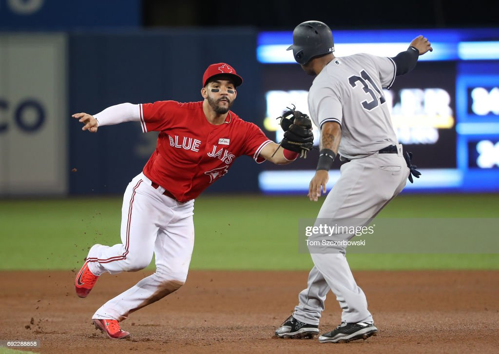 Devon Travis #54 of the Toronto Blue Jays fields a grounder and turns a double play by himself as he starts it by tagging out Aaron Hicks #31 of of the New York Yankees in the seventh inning during MLB game action at Rogers Centre on June 4, 2017 in Toronto, Canada.