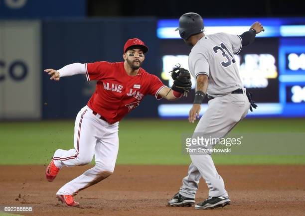 Devon Travis of the Toronto Blue Jays fields a grounder and turns a double play by himself as he starts it by tagging out Aaron Hicks of of the New...