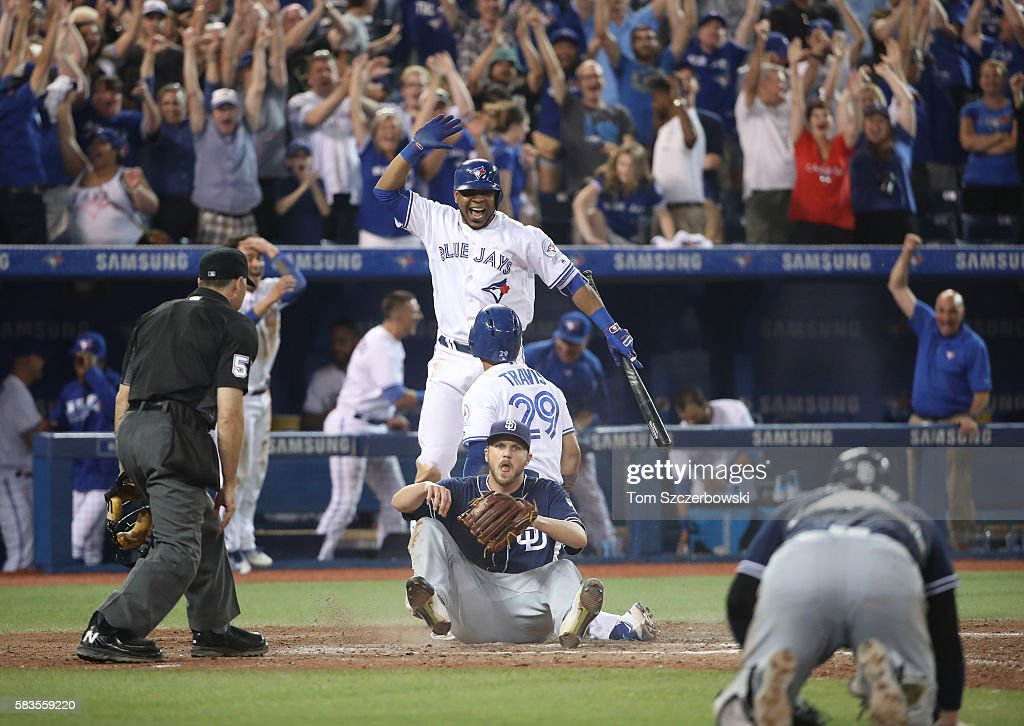 Devon Travis #29 of the Toronto Blue Jays is congratulated by Edwin Encarnacion #10 as Kevin Pillar #11 leaps in the air after their game-winning run scored on a wild pitch in the twelfth inning during MLB game action as Paul Clemens #47 of the San Diego Padres reacts on July 26, 2016 at Rogers Centre in Toronto, Ontario, Canada.