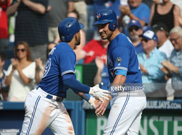 Devon Travis of the Toronto Blue Jays is congratulated by Luke Maile after hitting a tworun home run in the fifth inning during MLB game action...