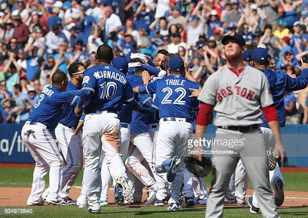 Devon Travis of the Toronto Blue Jays is congratulated by teammates on their walkoff victory during MLB game action as Craig Kimbrel of the Boston...