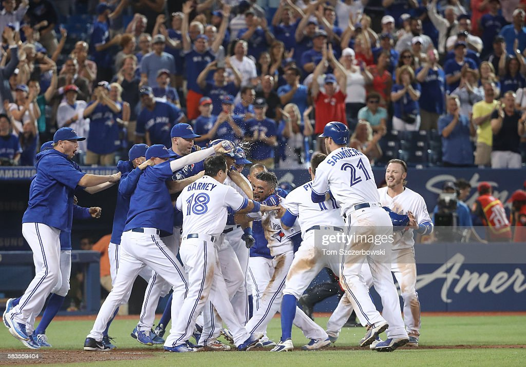 Devon Travis #29 of the Toronto Blue Jays is congratulated by teammates after scoring the game-winning run on a wild pitch in the twelfth inning during MLB game action against the San Diego Padres on July 26, 2016 at Rogers Centre in Toronto, Ontario, Canada.