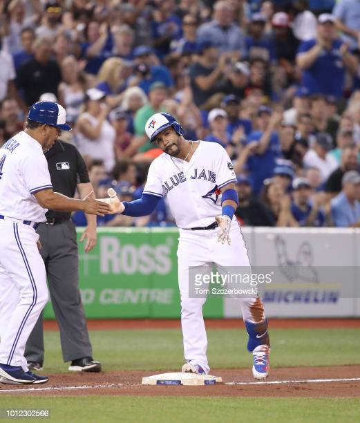 Devon Travis of the Toronto Blue Jays is congratulated by third base coach Luis Rivera after hitting an RBI triple in the seventh inning during MLB...