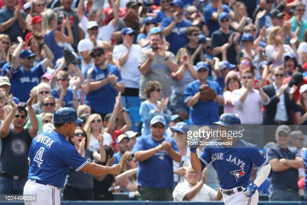 Devon Travis of the Toronto Blue Jays is congratulated by third base coach Luis Rivera as he circles the bases after hitting a threerun home run in...
