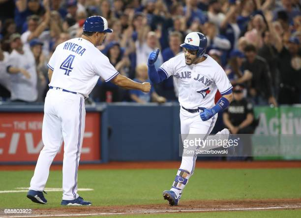 Devon Travis of the Toronto Blue Jays is congratulated by third base coach Luis Rivera after hitting a grand slam home run in the second inning...
