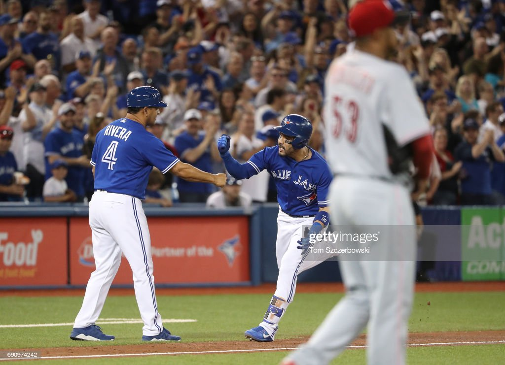 Devon Travis #29 of the Toronto Blue Jays is congratulated by third base coach Luis Rivera #4 after hitting a two-run home run in the seventh inning during MLB game action as Wandy Peralta #53 of the Cincinnati Reds reacts at Rogers Centre on May 31, 2017 in Toronto, Canada.