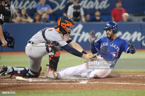 Devon Travis of the Toronto Blue Jays is tagged out at home plate while attempting to score as Grayson Greiner of the Detroit Tigers applies the tag...