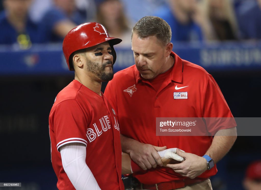 Devon Travis #29 of the Toronto Blue Jays reacts after being hit by a pitch on the hand as trainer Mike Frostad tends to him in the seventh inning during MLB game action against the New York Yankees at Rogers Centre on June 4, 2017 in Toronto, Canada.