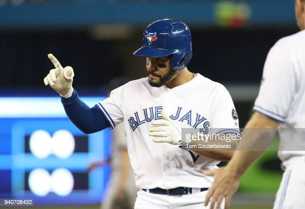 Devon Travis of the Toronto Blue Jays reacts after hitting an RBI single in the second inning during MLB game action against the New York Yankees at...